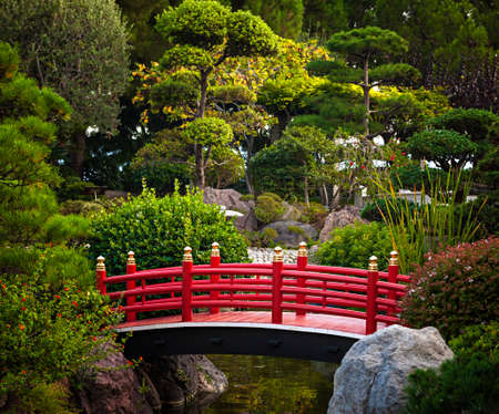 Red bridge over pond in Japanese garden. Monte Carlo, Monaco.