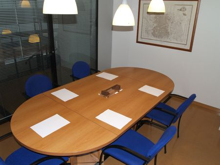 meeting room with a large wood table and five blue chairs