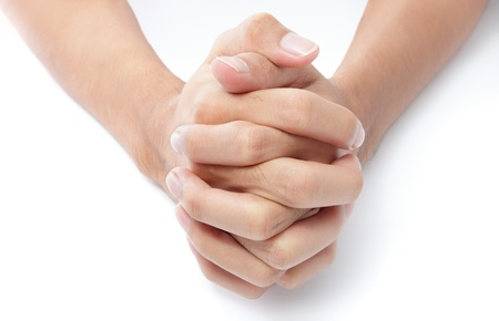 Close-up frontal top view of two hands folded with intertwined fingers praying on a white desktop.