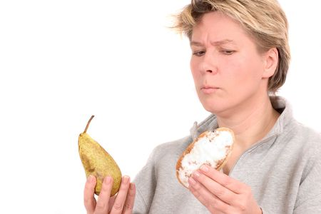 Woman being tempted to take the not to healthy bun or the fruit