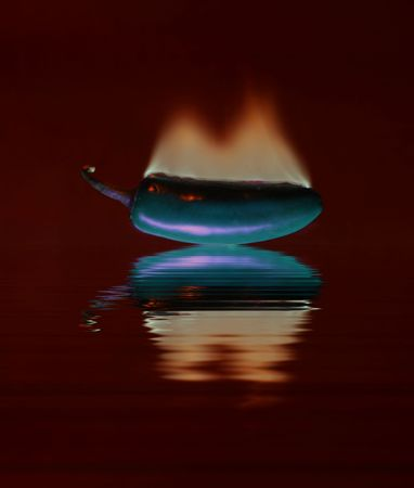 Long exposure of green jalapeno pepper on fire with reflection.  Narrow DOF.