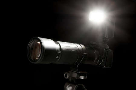Camera with flash going off isolated on black background