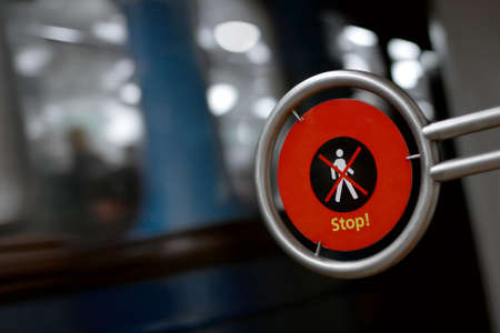 Warning sign far pedestrians with metro vehicle passing by with motion blur