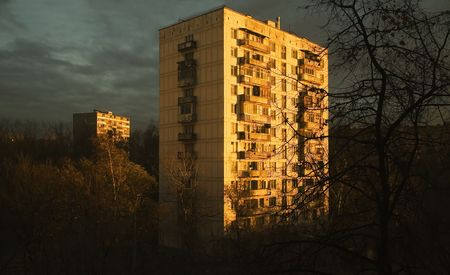 The sun on a dawn, shines on a panel high-rise building in suburbの写真素材