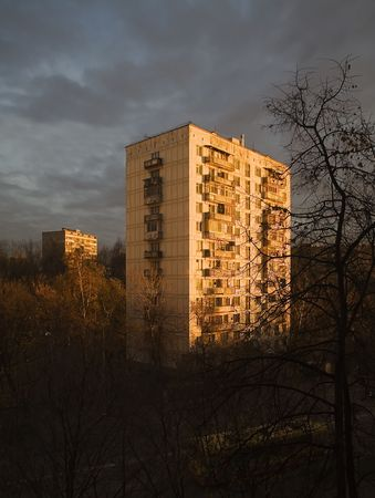 The sun on dawn shines on a panel high-rise building in suburbの写真素材