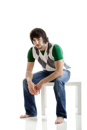 Young man portrait seated over a white background