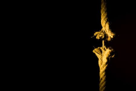 Frayed rope breaking on a dark background