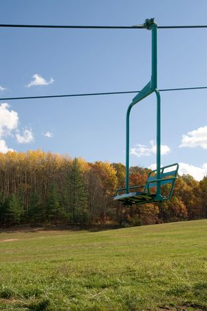 Lonely ski area chairlift with autumn trees