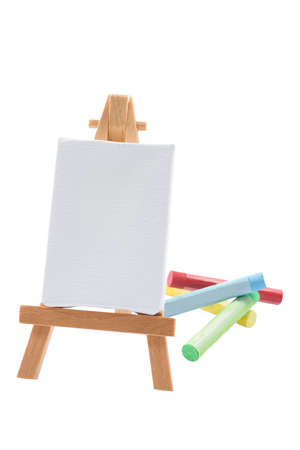 A blank stretched canvas on an easel with soft painted pastel sticks