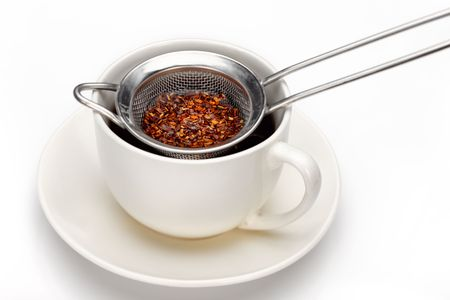 Making tea with a traditional strainer (focus on tea leaves)