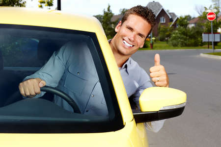 Happy young man driver in a new car.