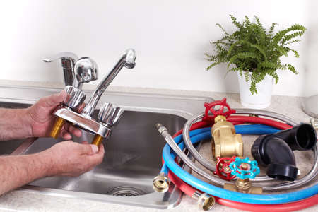 Hands of professional Plumber with a water tap