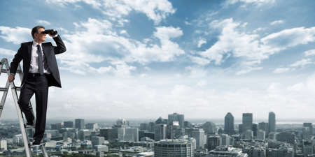 Business man with binoculars spying on competitors