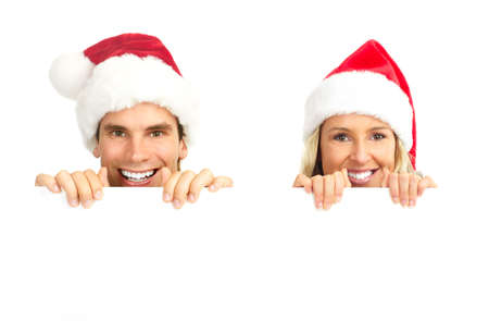 Young happy couple in Christmas hats. Isolated over white background