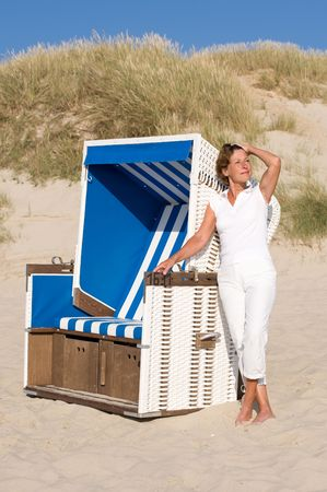 Active senior woman with white clothes is standing at a beachchair.