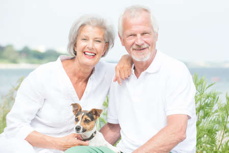 Smiling and actice senior couple with dog