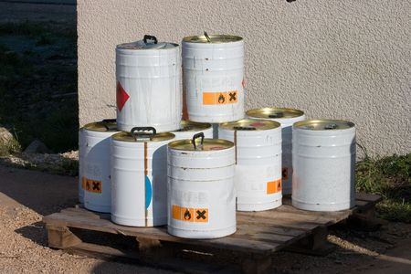 Metal containers of industrial chemicals sitting outside a plant.