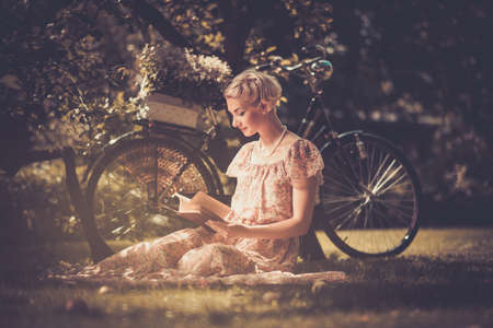 Blond beautiful retro woman reading book on a meadow