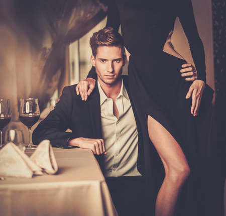 Sexy well-dressed young couple in luxury interior