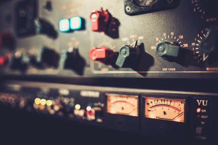 Close-up amplifier equipment with sliders and knobs at boutique recording studio.