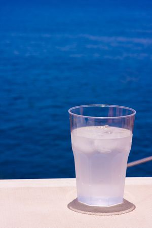 Glass of cold water with ice on blue water background