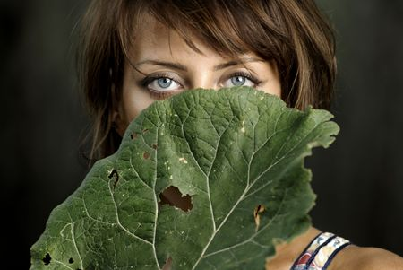 Half-face of the beautiful lady hidden by the burdock leaf