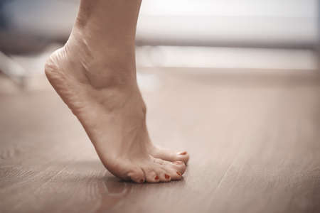 Feet of woman standing on tiptoe at homeの写真素材