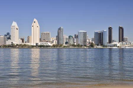 Office towers reflect in the water of San Diego Bay.