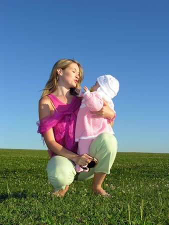 mother with baby on sunset blue sky green grass
