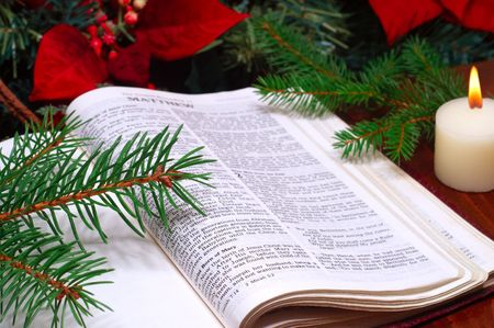 Bible open to the Christmas passage of Matthew 2 with candle, poinsettia, and evergreen sprigs