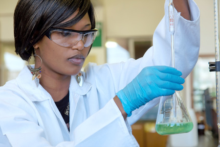 Focused African female researcher works with a glass in the lab.