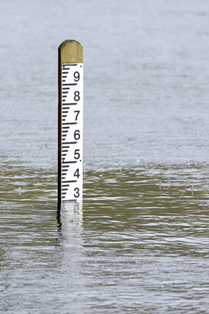 Flood level depth marker post with rain falling into the surrounding water
