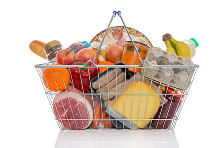 Studio shot of a shopping basket full of food including fresh fruit, vegetables, meat, pizza and dairy products. Isolated on a white background.の写真素材