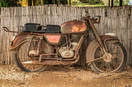 the old, rusty motorcycle on a street