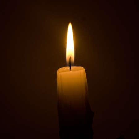 burning candle over black background
