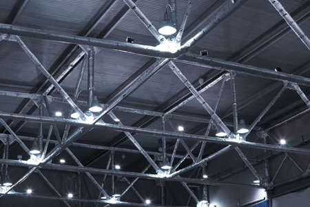 powerful lamps and metallic pipes under ceiling of industrial building
