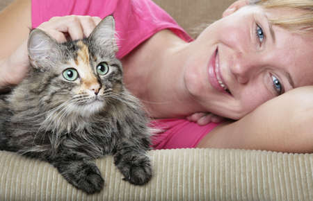 Pretty girl and cute cat on the sofa