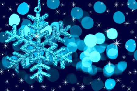 Christmas decoration snowflake  on defocused lights and stars background / blue toned
