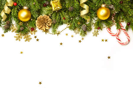 Christmas tree branches with golden baubles, stars, snowflakes isolated on white  -  horizontal border