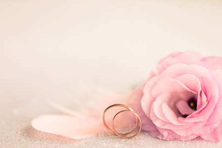 Wedding  Background with gold Rings, Eustoma rose flower and light pink feather