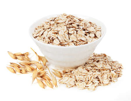 Rolled oats in a plate isolated on white background