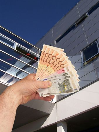 An image of a hand holding out a wad of cash in front of a corperate office building facility
