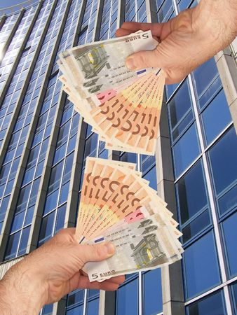 An image of hands holding out a wads of cash in front of a corperate office building facility
