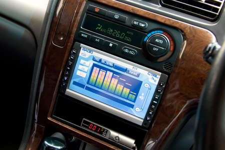 Modern luxury car interior, tv/dvd/audio system with monitor and climat control view.