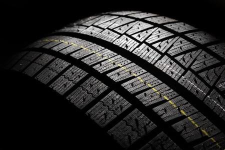 Part of brand new modern winter car tyre on a black background. Studio shot.