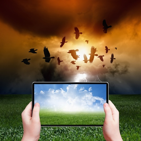 Photo pour Concept of augmented reality - abstract tablet pc in hands, sunny weather, stormy weather, flock of flying ravens, crows in dark sky with lightning - image libre de droit