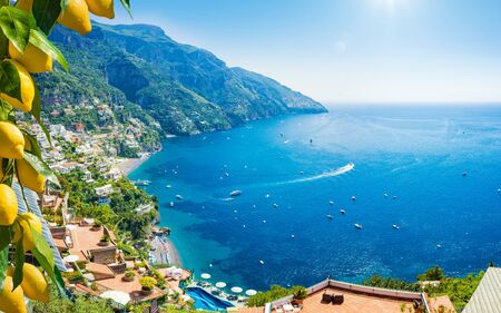 Foto de Beautiful Positano with comfortable beaches and clear blue sea on Amalfi Coast in Campania, Italy. Amalfi coast is popular travel and holyday destination in Europe. Ripe yellow lemons in foreground. - Imagen libre de derechos