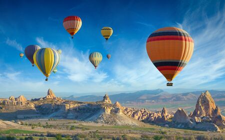Photo for Surise view of unusual rocky landscape in Cappadocia, Turkey. Colorful hot air balloons fly in blue sky over amazing valleys with fairy chimneys in Cappadocia. - Royalty Free Image