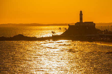 SALVADOR, BRAZIL: Portrait of the Farol da Barra Salvador Brazil lighthouse. Beautiful landscape with verm at sunset. America
