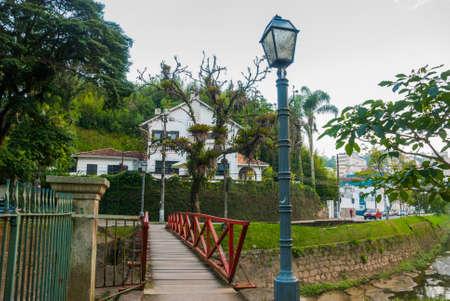 Photo pour PETROPOLIS, RIO DE JANEIRO, BRAZIL: Beautiful old house and a wooden bridge over the pond in Petropolis, Rio de Janeiro, Brazil - image libre de droit